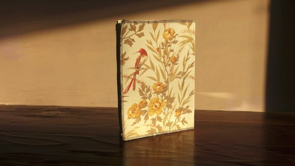 מחברת משבצות 100 דפים מחופה בד פרחוני עם ציפור בחזית ובגב