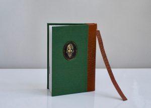 הספר מוכן עם הסימניה מהעור והמטבע בחזית